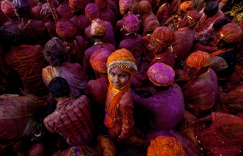 A child looks on as Indian villagers sme