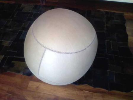 Rivestimento della palla ispirata alle geometrie della pallina da baseball in vera pelle color cammello con cuciture a contrasto color amaranto