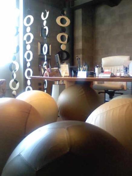 Vista di insieme: primo piano, in marrone, palla da calcio, a sx palla da baseball con cuciture a contrasto amaranto, nello sfondo altre prove